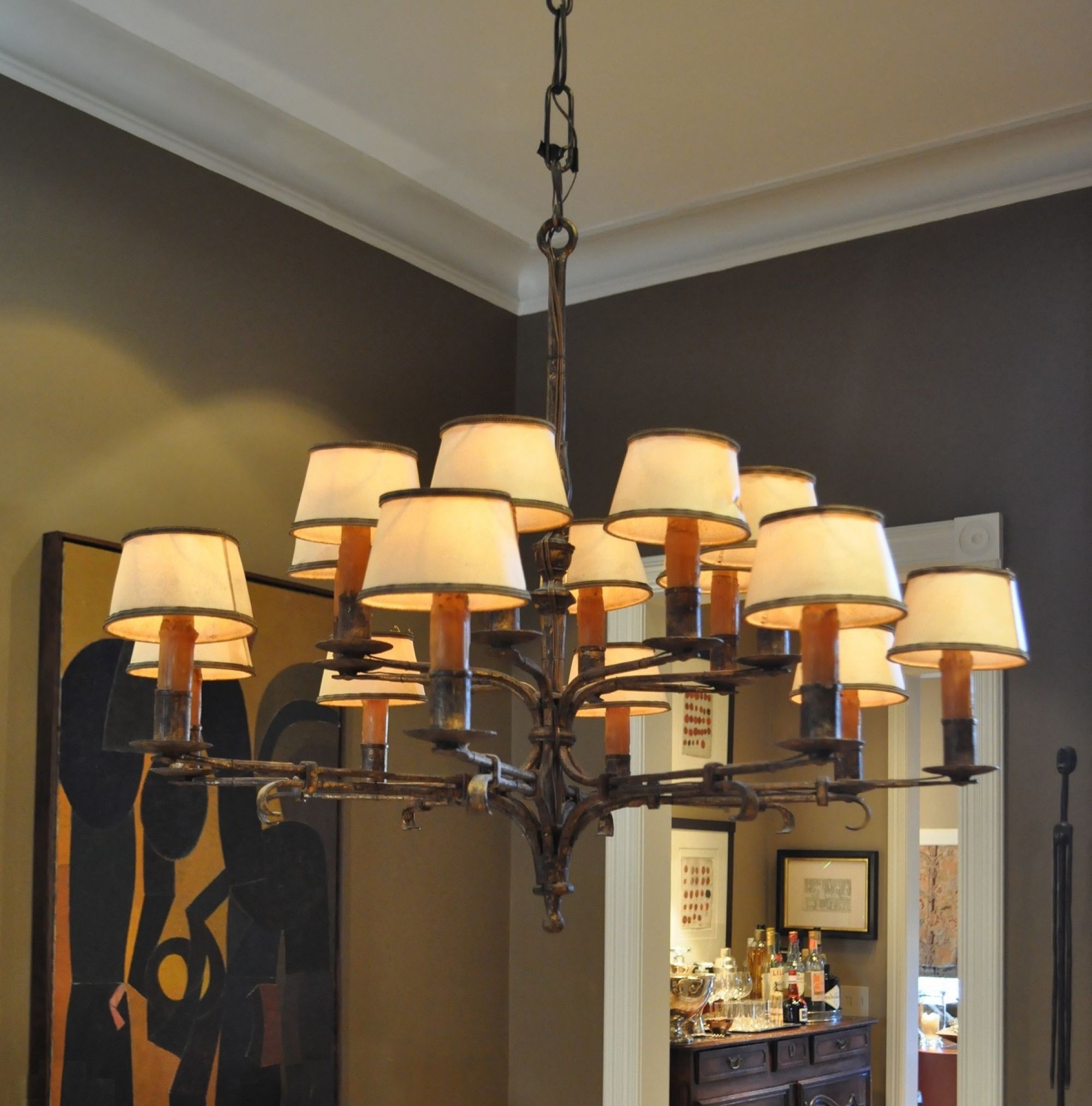 This gilded wrought iron chandelier has parchment shades and real wax candle sleeves.