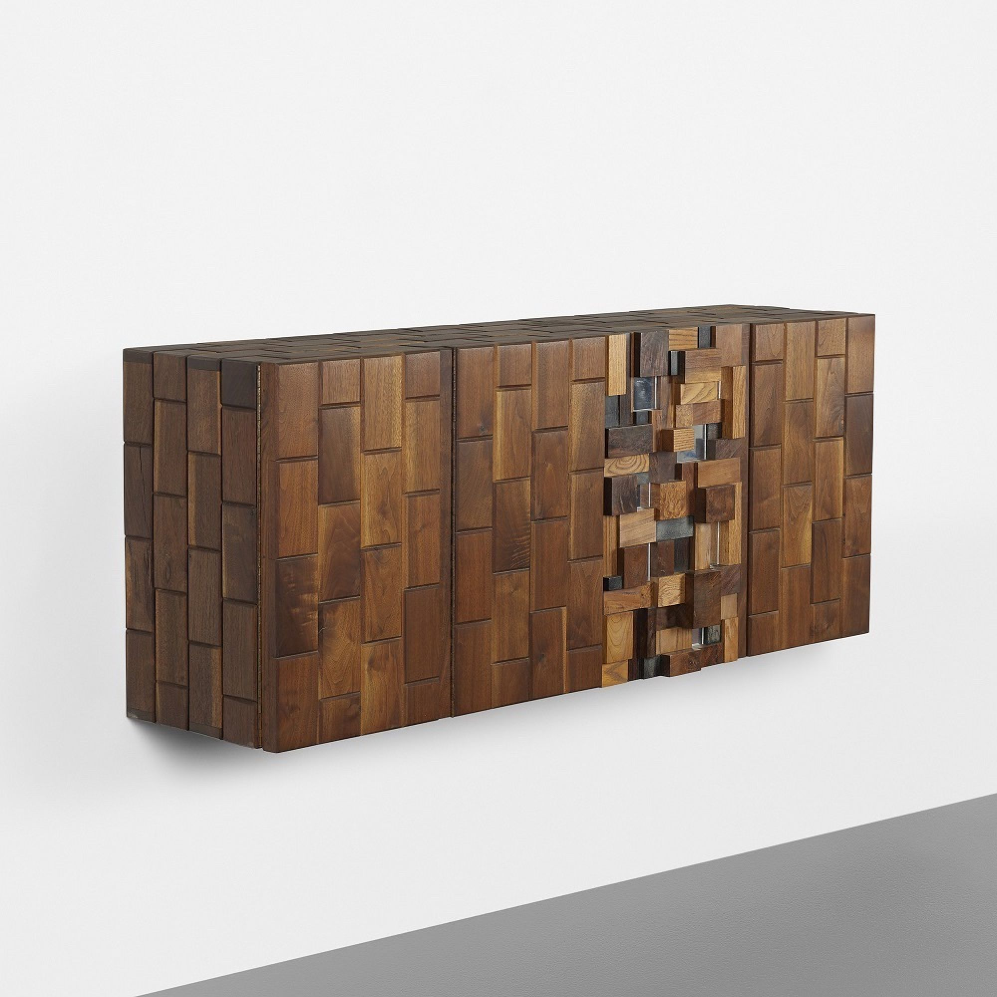 Phillip Lloyd Powell's dramatic wall-mounted cabinet sports a sculptural collage of exotic woods and reminds us of the brawny but glamorous case goods of furniture-maker Paul Evans.